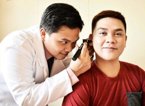 audiologist performing otoscopy